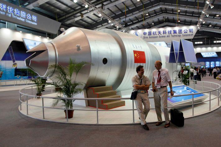 Visitantes se sientan junto a un modelo de la estación espacial Tiangong-1 de China en la ...