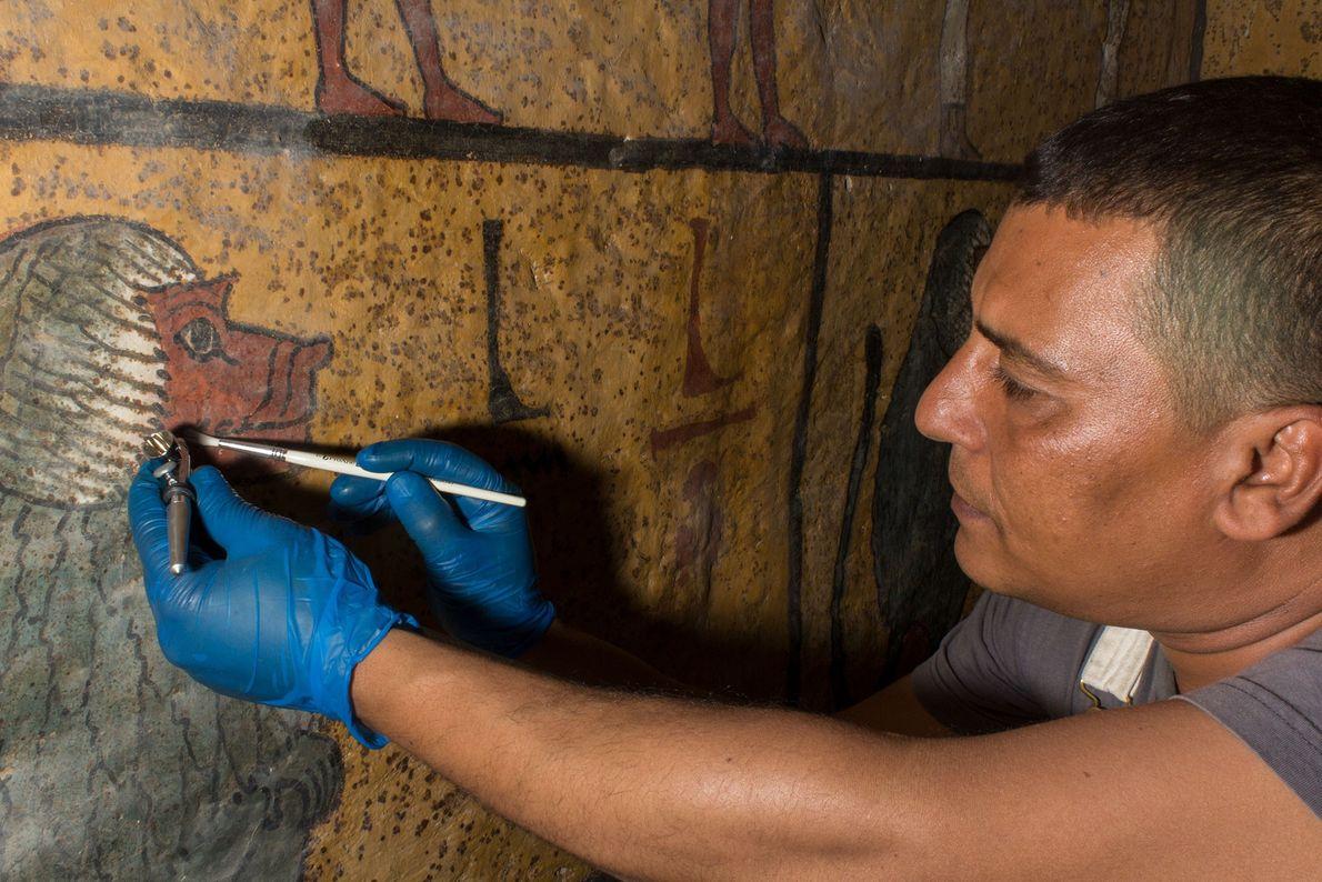 Un conservador elimina suavemente el polvo pegajoso que se ha acumulado en las superficies pintadas de ...