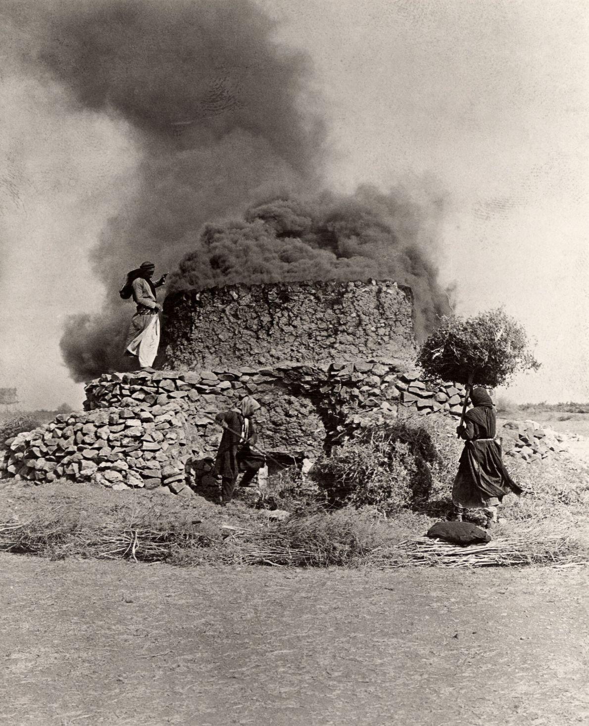 Los aldeanos llevan arbustos a un horno de cal humeante para crear combustible en Homs, Siria, ...