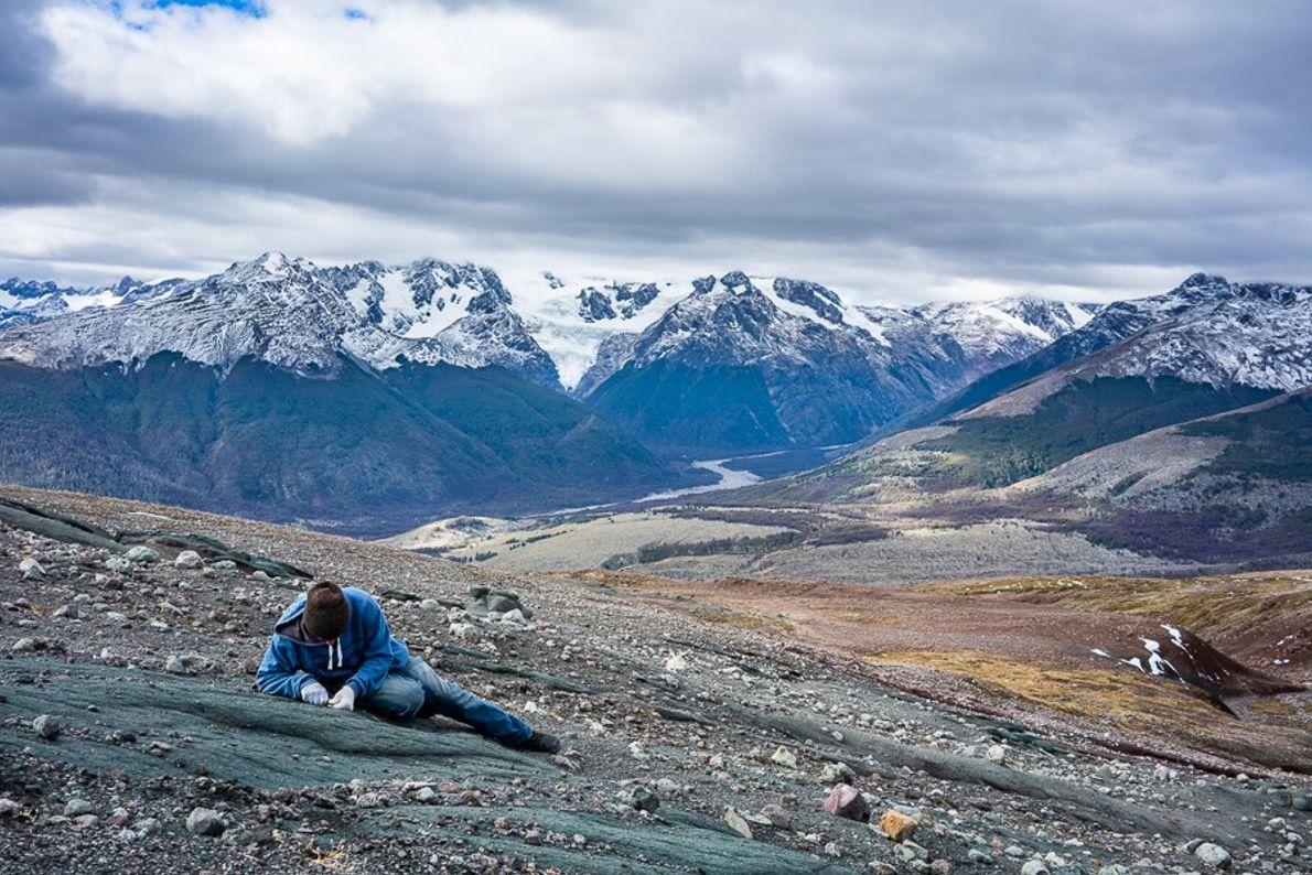 Santiago Miner busca pequeños huesos en las montañas de la Formación Toqui. Detrás, se pueden apreciar ...