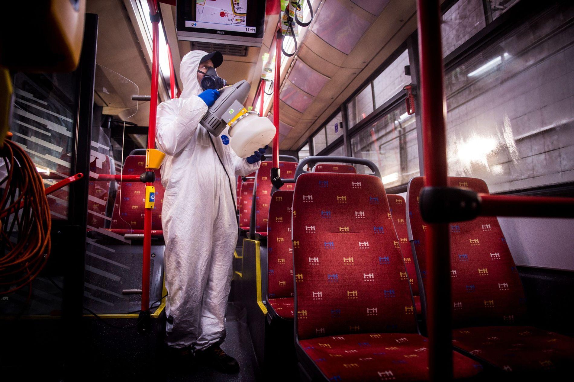 Cubierto con un traje protector, un trabajador desinfecta el interior de un autobús público en una ...