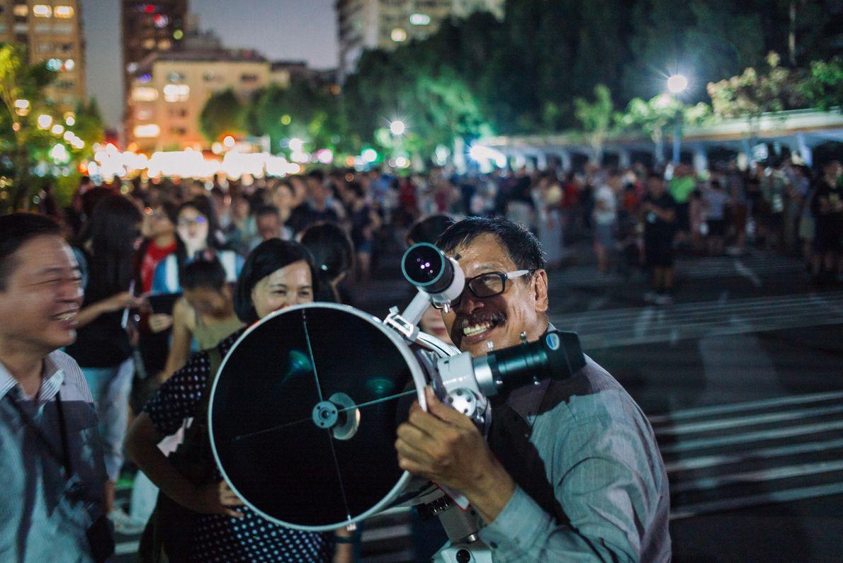 La gente coloca sus telescopios para presenciar el raro eclipse lunar total cerca del monumento conmemorativo ...