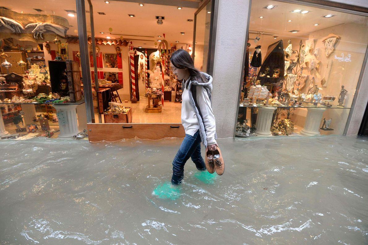 Una mujer camina en una calle veneciana inundada. Según los funcionarios de la ciudad, alrededor del ...