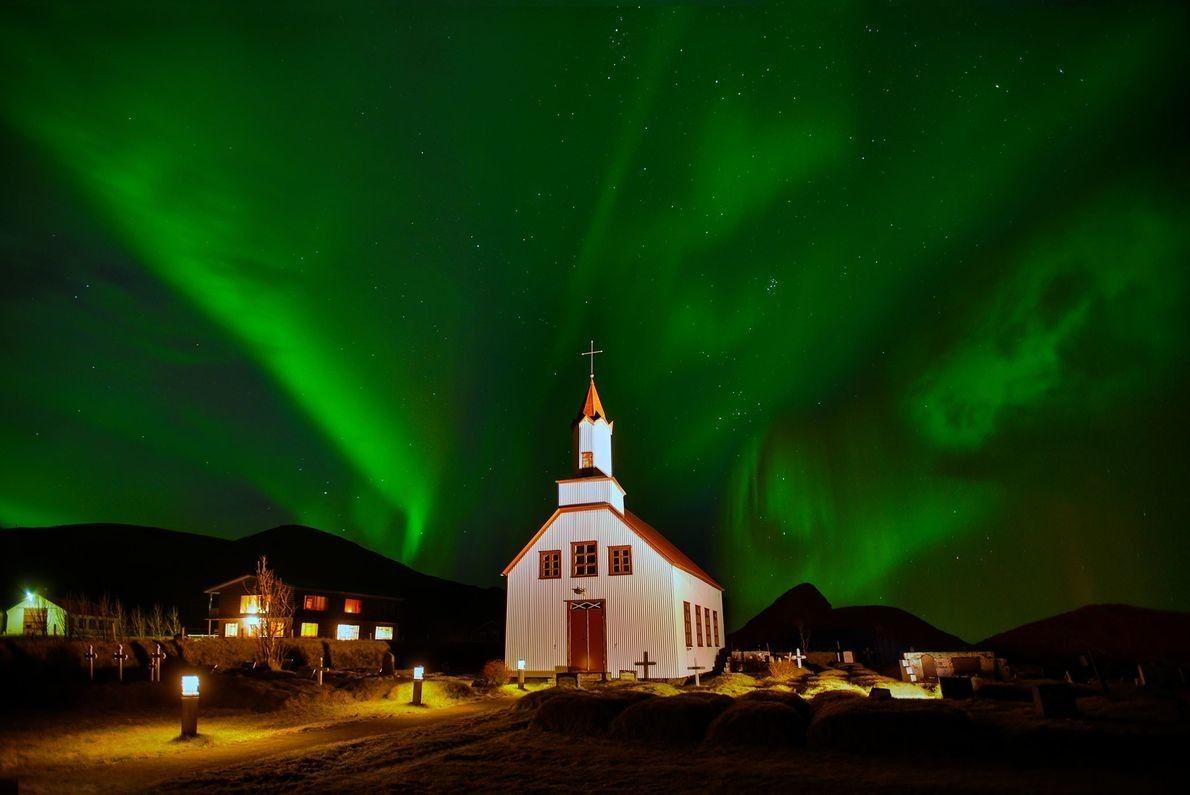 Las luces del norte tiñen el cielo de verde tras una iglesia en Islandia.