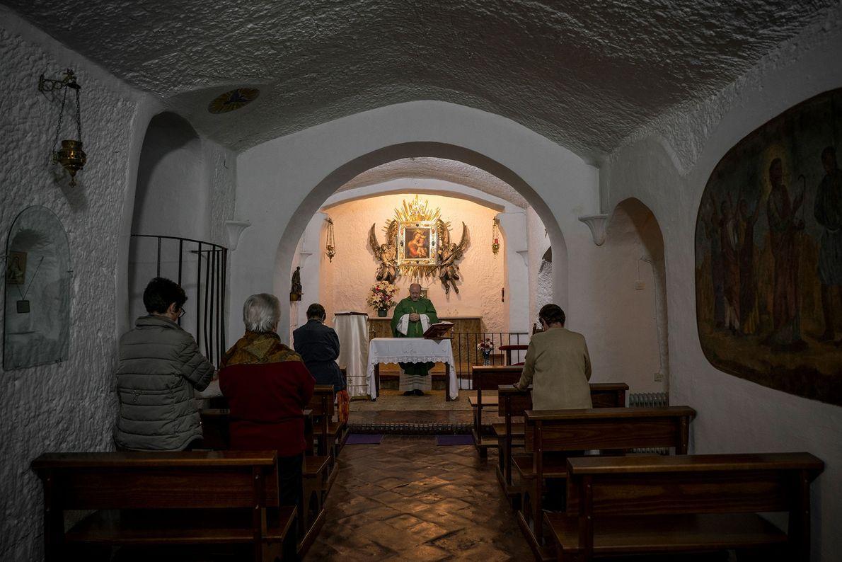 Un sacerdote oficia una misa en Nuestra Señora de Gracia, una iglesia católica subterránea en Guadix. ...