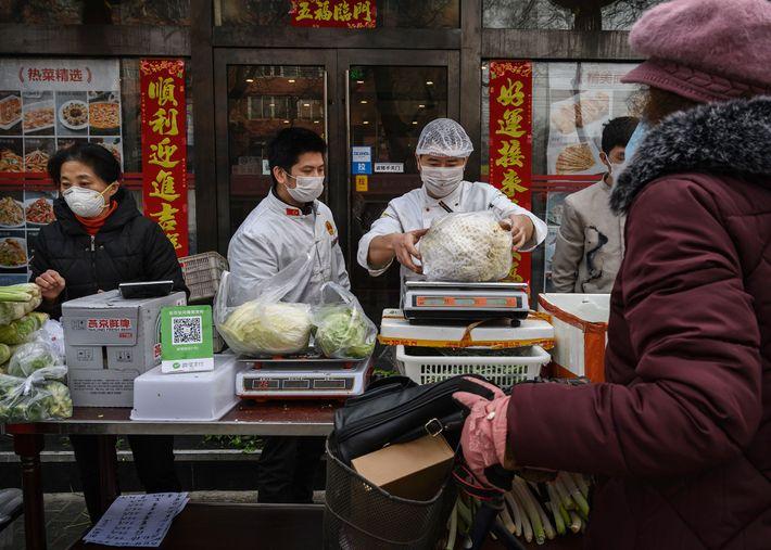 Vendedores en Pekín usan máscaras protectoras mientras venden vegetales. Un estudio de 2014 halló que solo ...