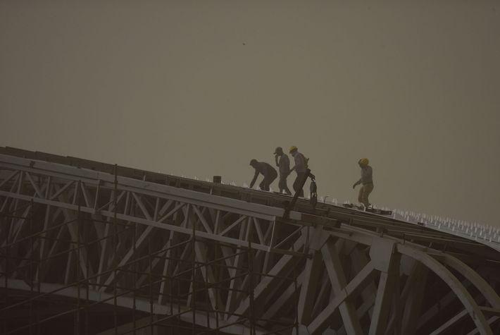 Trabajadores en el estadio Noida en medio de una repentina y espesa tormenta de polvo el ...