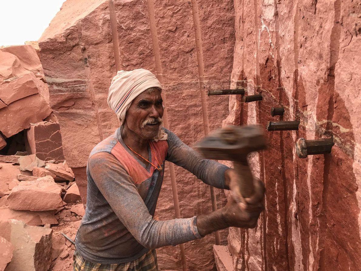 Battu Singh (45) trabaja con un martillo sobre la cara de una roca para luego colocar ...