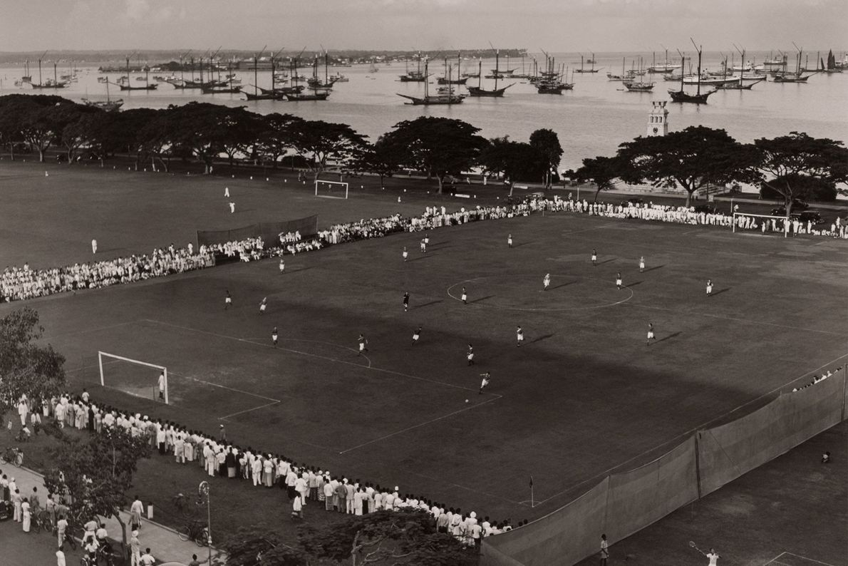 Espectadores rodean el campo de juego que se encuentra al lado de un puerto en las ...