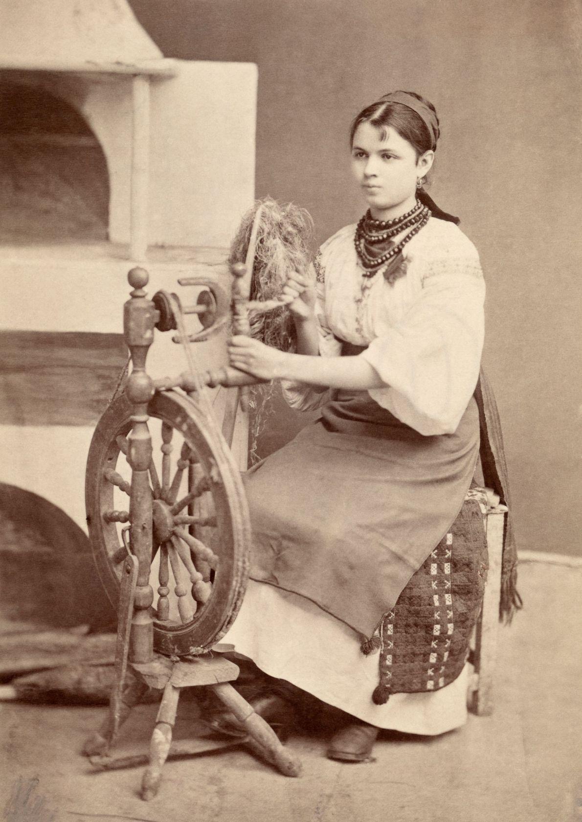 Una mujer ucraniana con vestimenta tradicional trabaja en una rueca en 1918.