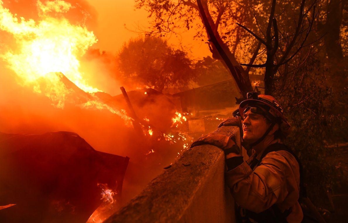 El alcalde de Malibú y el bombero Rick Mullen inspeccionan una casa en llamas atrapada en ...
