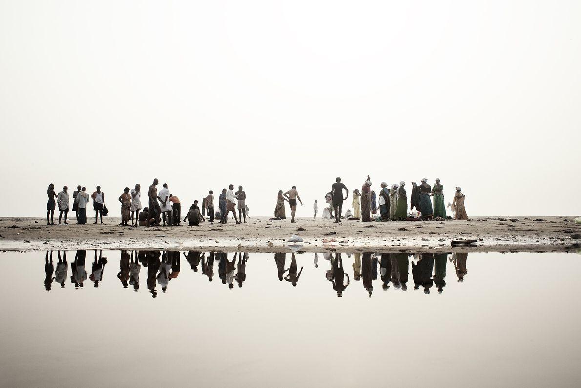 Devotos hindúes en las riberas del Ganges se preparan para bañarse en el agua del río ...