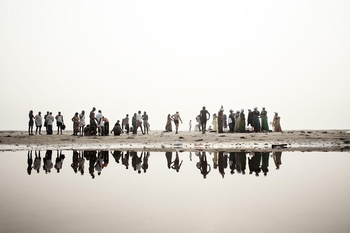 Devotos hindúes en las riberas del Ganges se preparan para bañarse en el agua del río …
