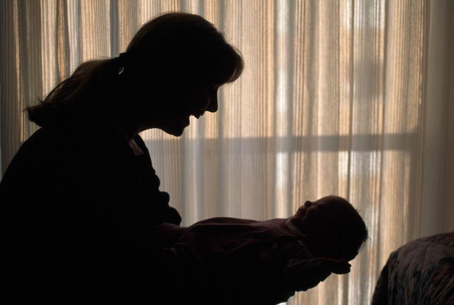 Una madre sostiene a su bebé en sus brazos.