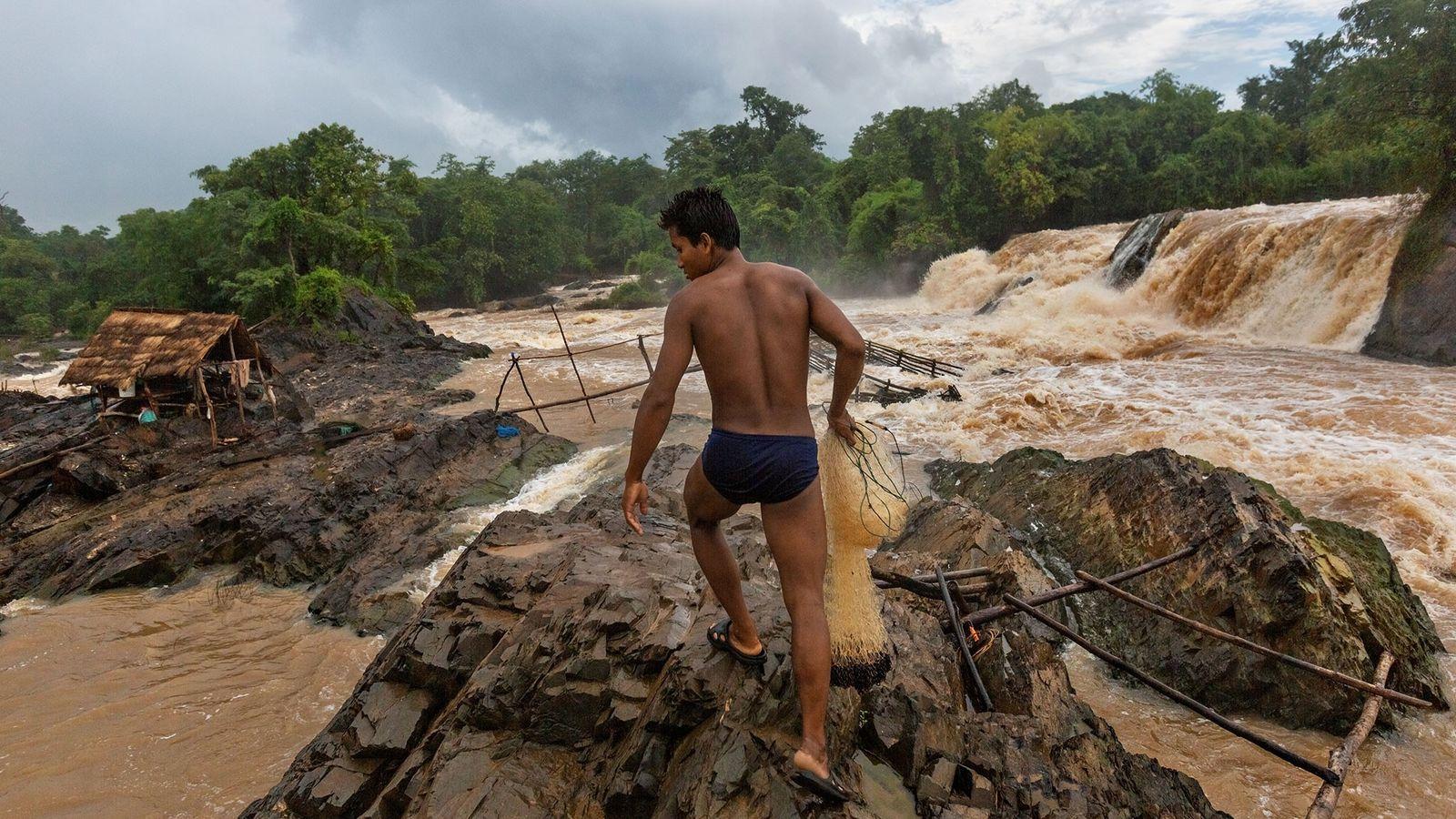 Un pescador se prepara para arrojar sus redes en una zona de las Cataratas de Khone ...