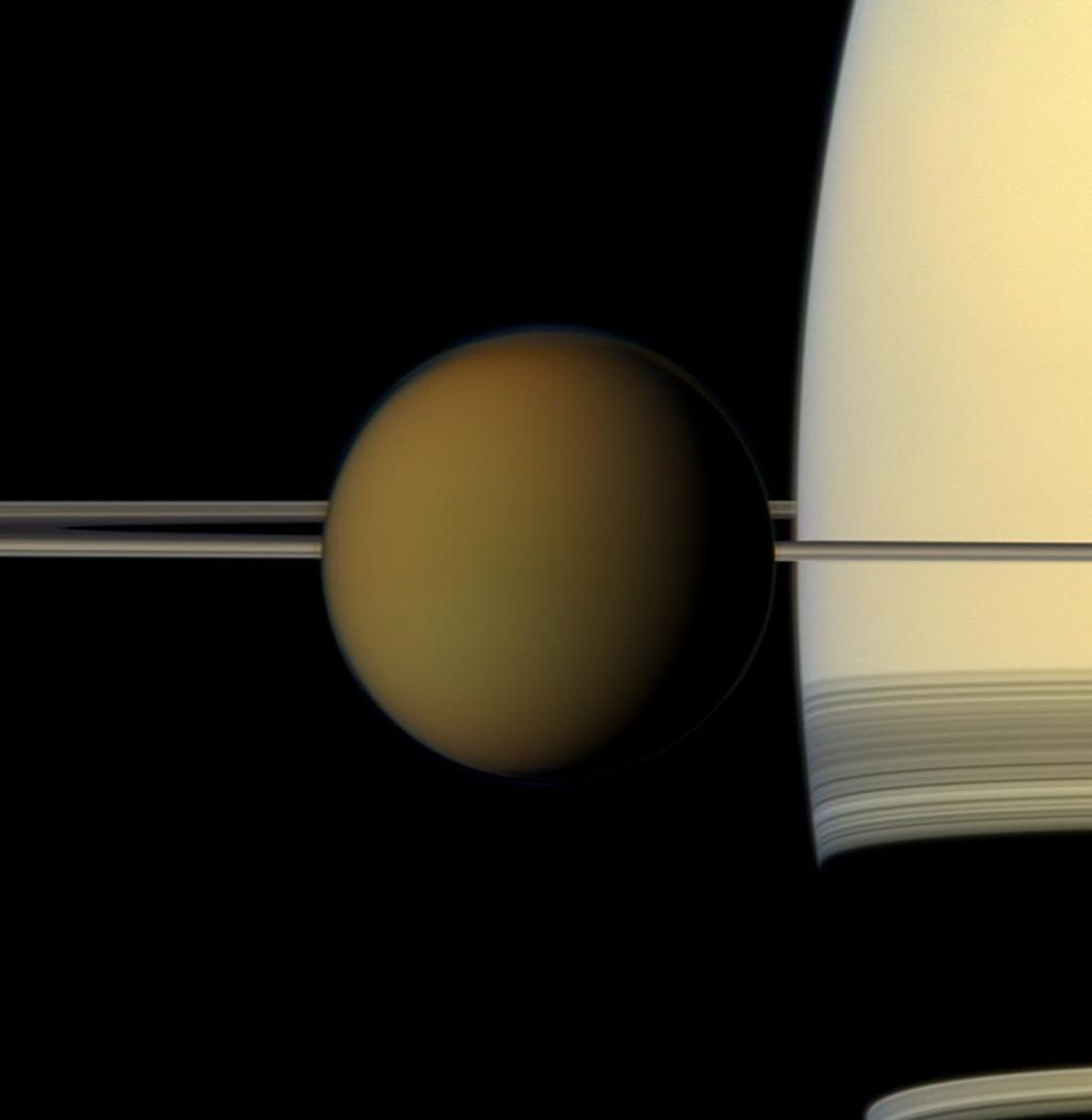 El vistoso orbe de la luna más grande de Saturno, Titán, pasa frente al planeta y ...