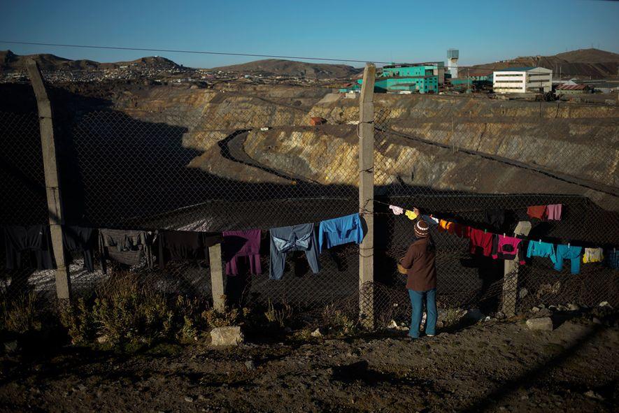 La ropa está tendida para secarse en una cerca que separa el vecindario de Yanacancha de ...