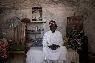Mbacke se sienta en su cama dentro de su casa en Sacromonte, donde ha vivido durante ...
