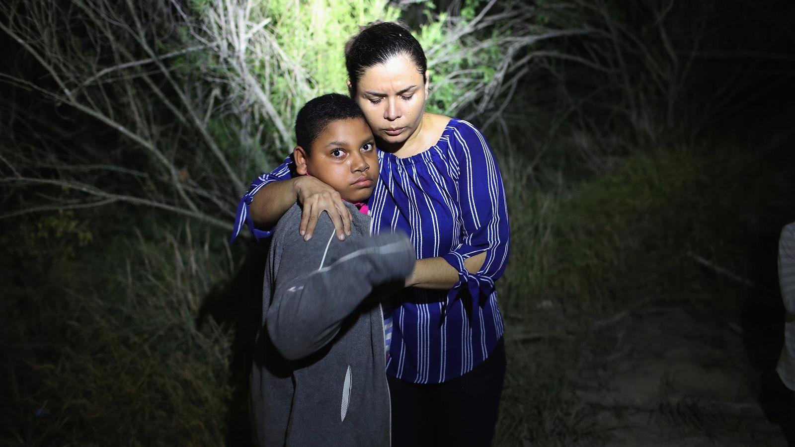 Un foco de la Patrulla Fronteriza de los Estados Unidos ilumina a una madre hondureña y ...