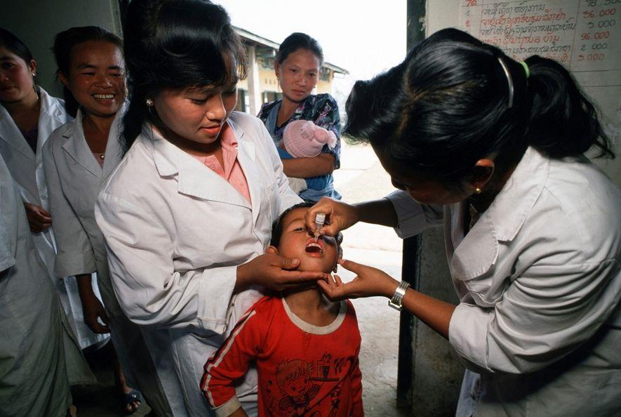 Los trabajadores de salud en el norte de Laos inoculan a niños en 1991 como parte ...