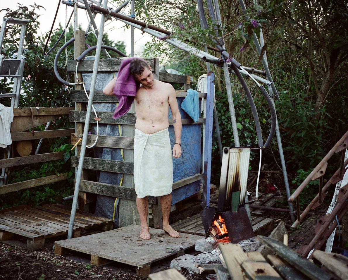 Un hombre se seca después de bañarse en las duchas de Grow Heathrow. El grupo calienta ...