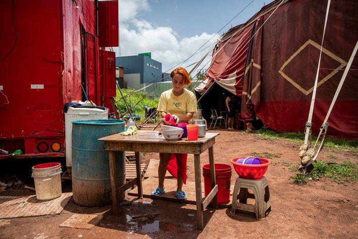 Lilian limpia los platos en la cocina improvisada al lado de donde viven. Los artistas vendieron ...
