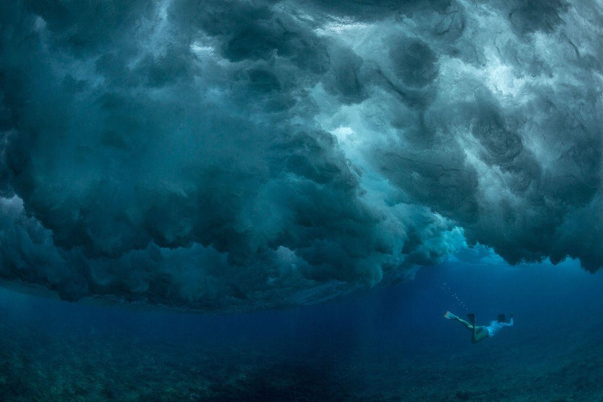 Un buzo aguarda bajo el agua a que rompa la ola en la isla de Oahu, ...