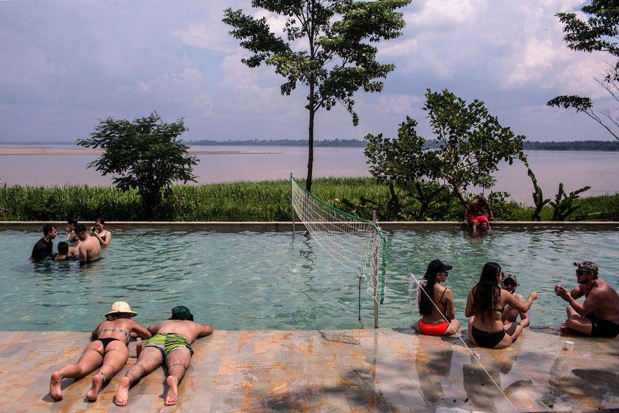 Los turistas descansan en la pileta del On Vacation Amazon, un resort colombiano que queda justo ...