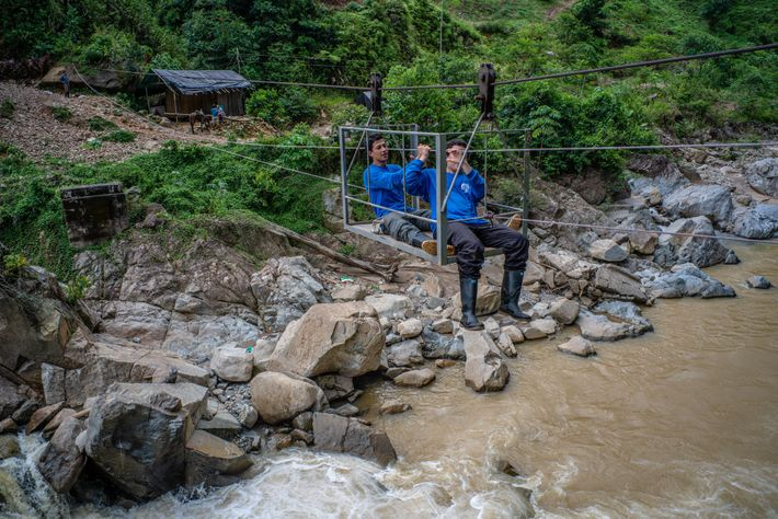 Dos biólogos del equipo cruzan el río usando tirolesas que los granjeros usan a diario.