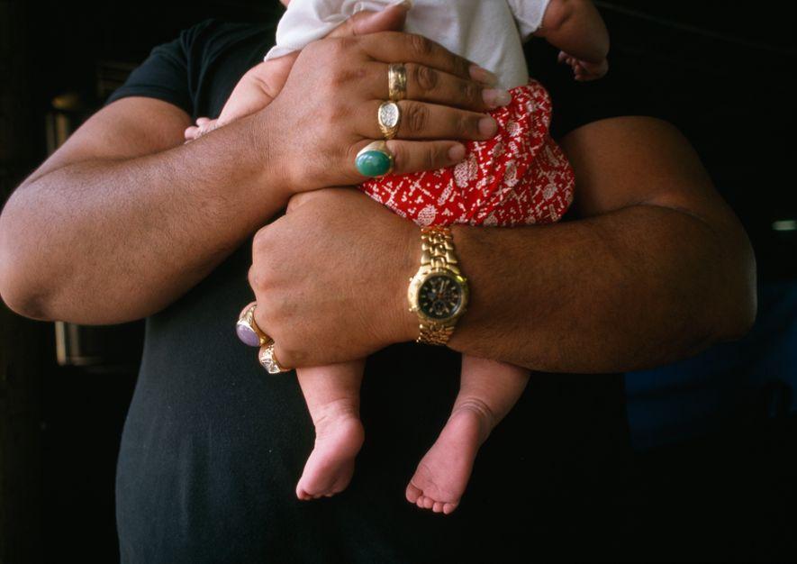 El músico Kurt Kipapa, padre de 10 niños, abraza al más pequeño de ellos.