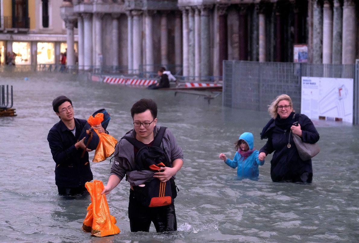 La gente camina penosamente por la plaza, tratando de mantener sus pertenencias secas.