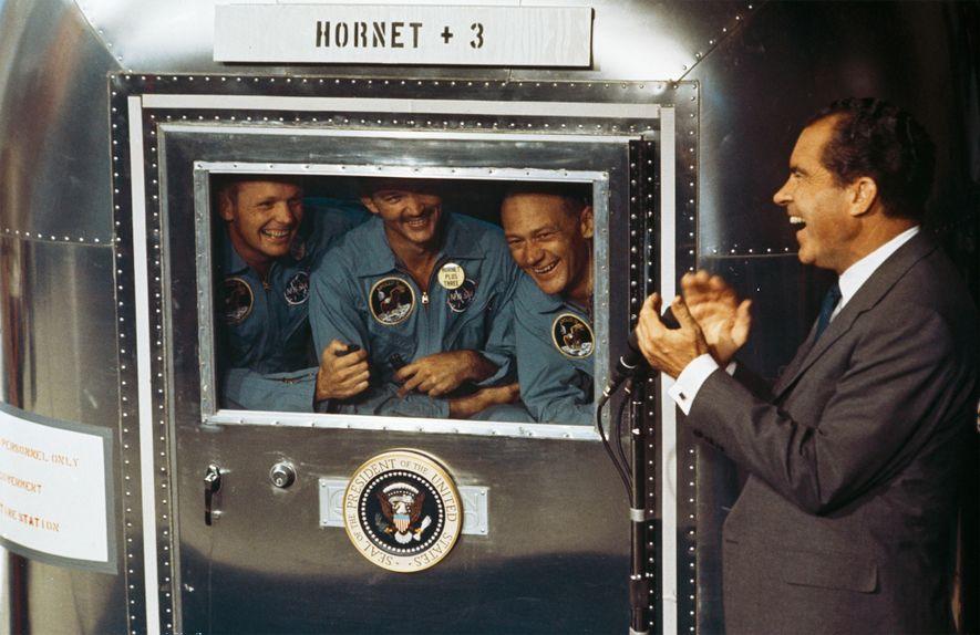 Tras regresar a la Tierra, Aldrin (a la derecha) y los otros astronautas de la Apolo 11 fueron puestos en cuarentena en caso de haber traído a la Tierra patógenos desconocidos. En la imagen, hablan con el presidente Richard Nixon poco después de amerizar en el Pacífico.