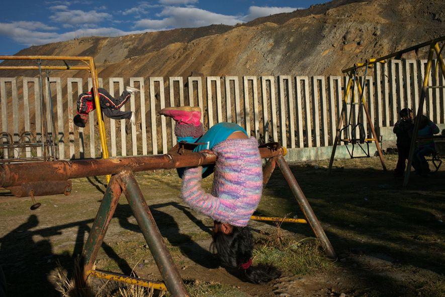 Pilas de relaves de la mina contaminada se asoman en un patio de juegos en el ...
