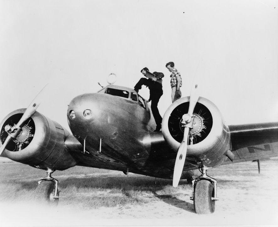 Earhart, derecha, y su copiloto Fred Noonan se preparan para ingresar a Electra en una parada ...