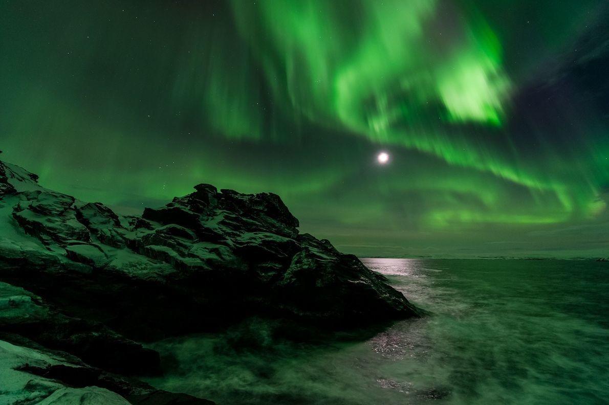 La Luna resplandece a través de una aurora boreal vista desde Laksefjorden en Noruega.