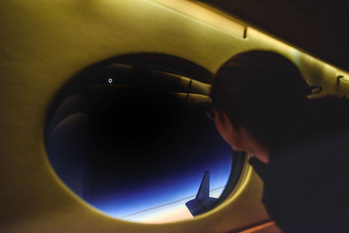 A bordo del avión siguiendo la sombra del eclipse, Tafreshi captura a un pasajero mirando el ...