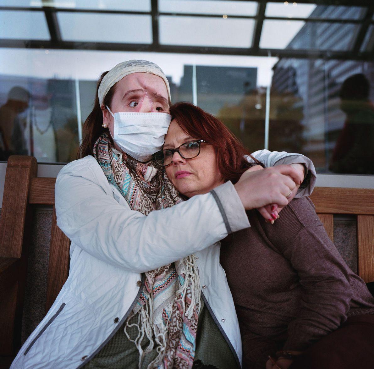 Katie abraza a su madre mientras están paradas fuera de la clínica de ojos de la ...
