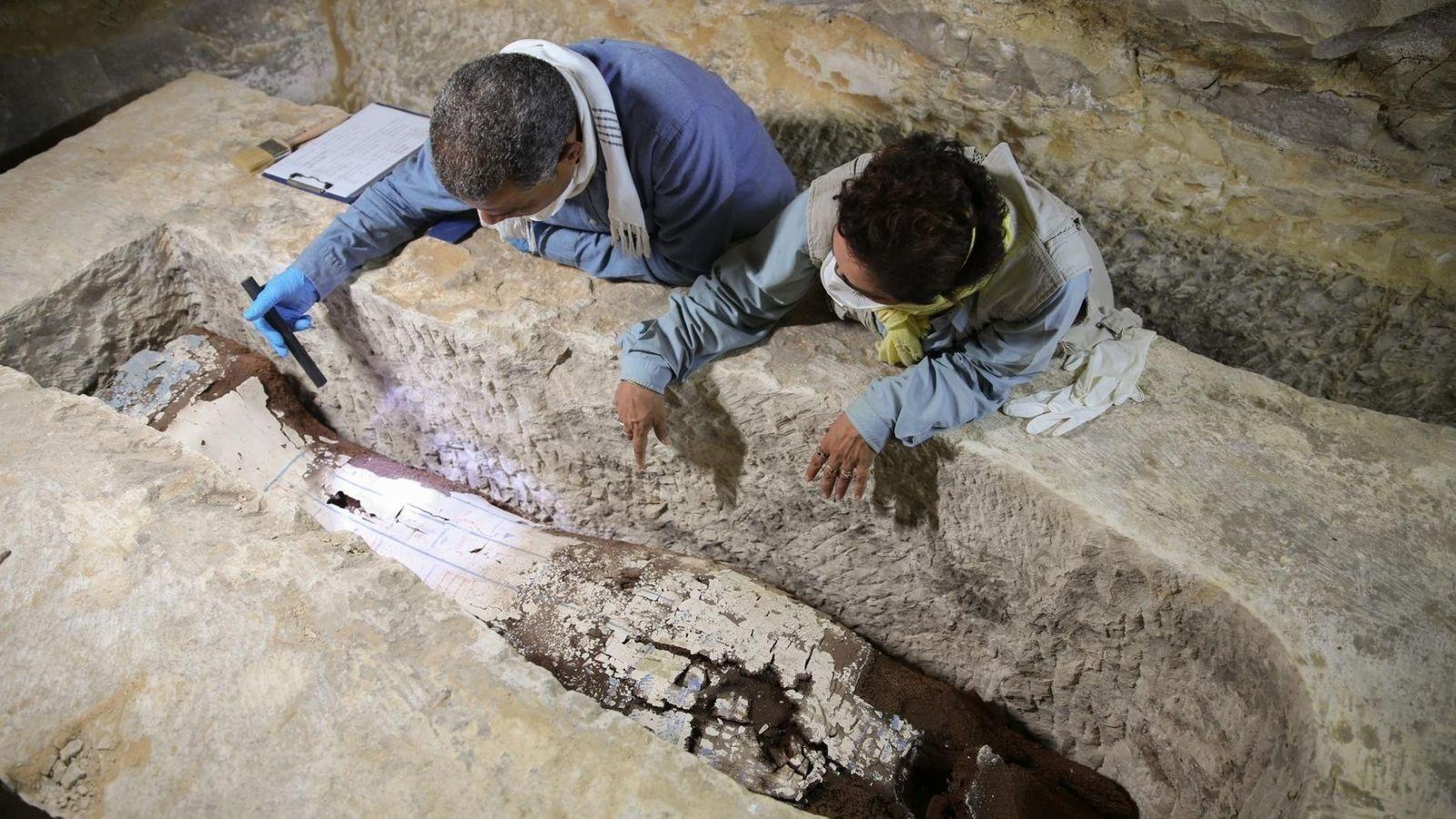 En una tumba en las profundidades del desierto, el egiptólogo Ramadaan Hussein (izq.) y la especialista ...