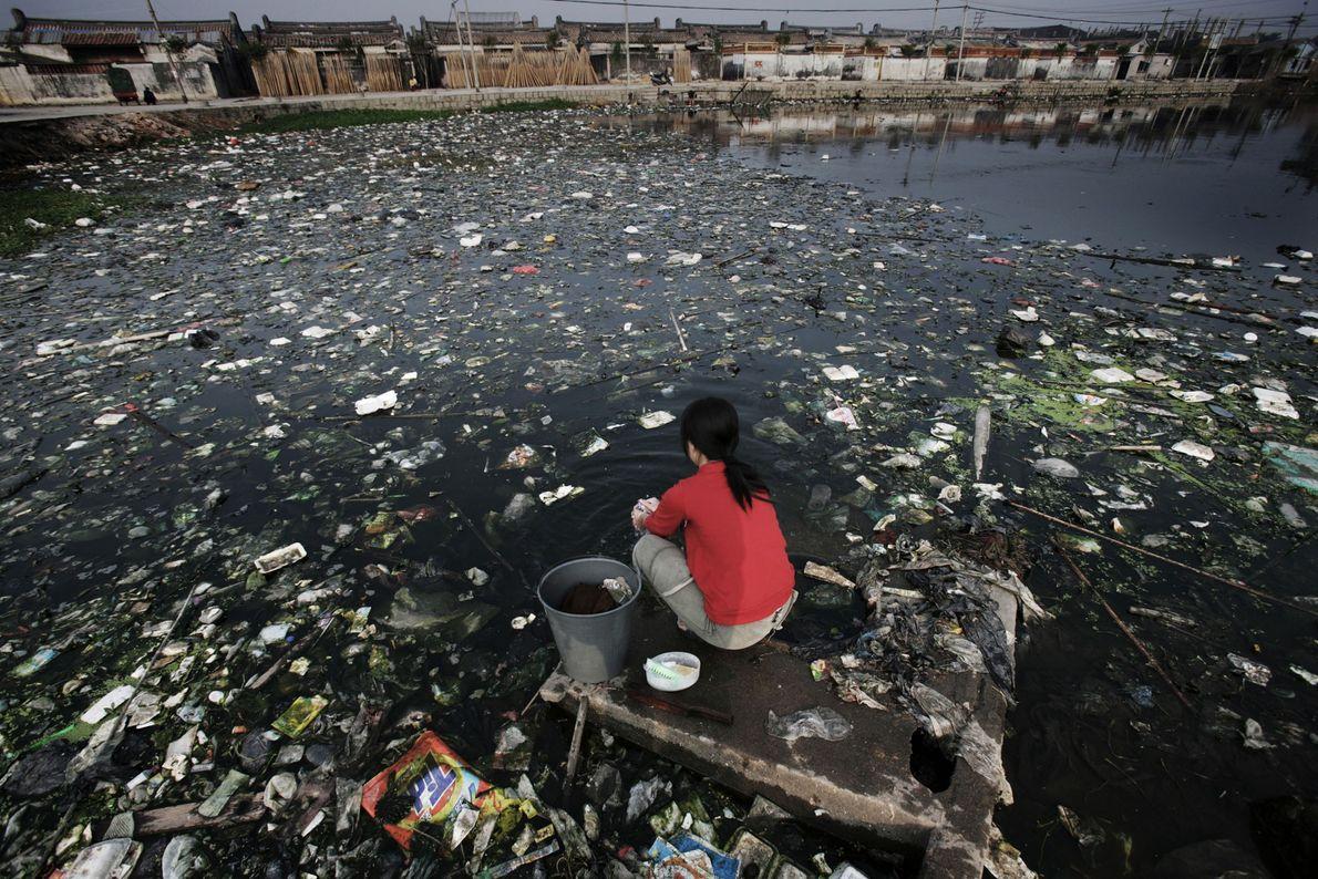 Esta mujer está sentada en un saliente al borde de uno de los ríos más contaminados ...