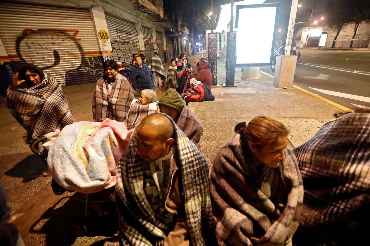 Las personas se reúnen en una calle en la Ciudad de México, México. Alrededor de un ...