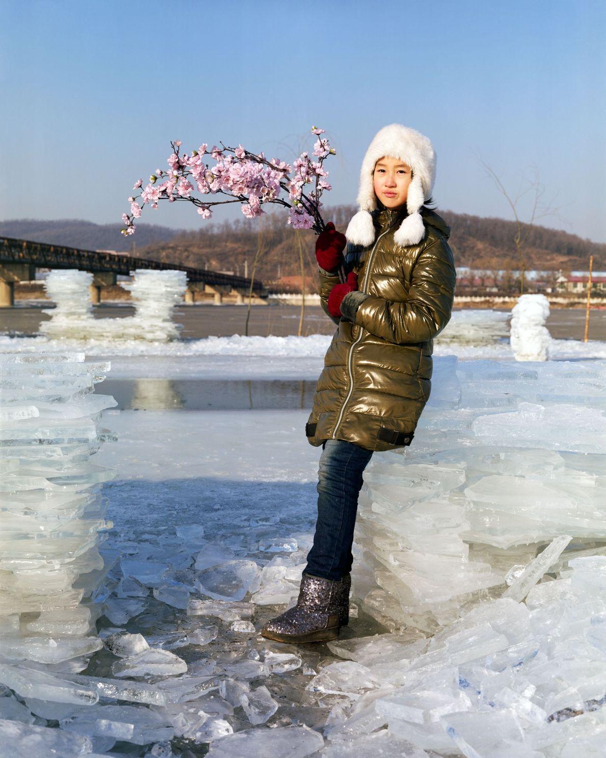 Yuting, de 10 años, en la orilla del río Hun con un ramo de flores artificiales ...