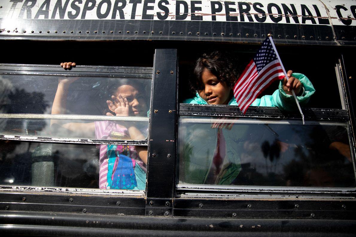 Las niñas a bordo de un autobús escolar flamean banderas estadounidenses cuando se mudan a un ...