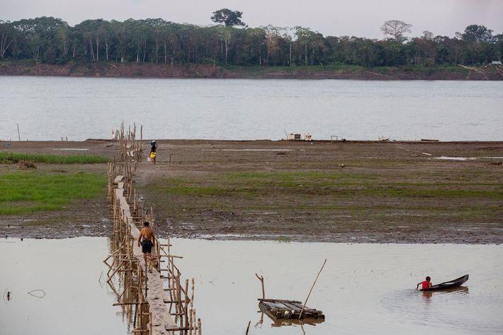 Una larga pasarela conecta Puerto Alegría con el Río Amazonas. Del otro lado del río está ...