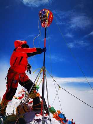 Un miembro de un equipo chino coloca un marcador en la cima del Monte Everest el ...