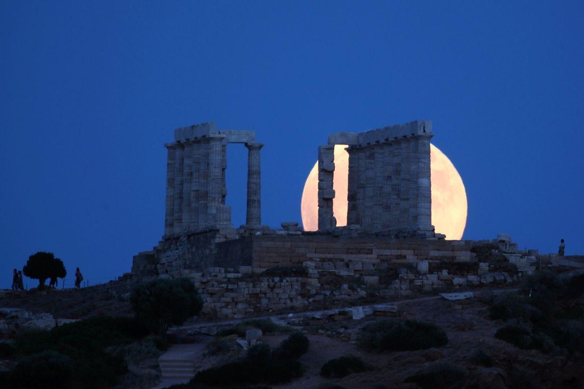 La luna llena se eleva tras el antiguo Templo de Poseidón en el cabo de Sunión, ...