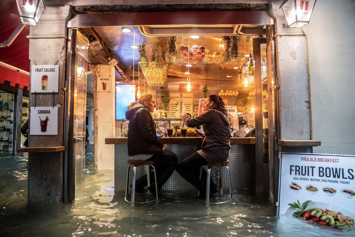 Los lugareños hacen una pausa para tomar una copa a pesar de la altura del agua.