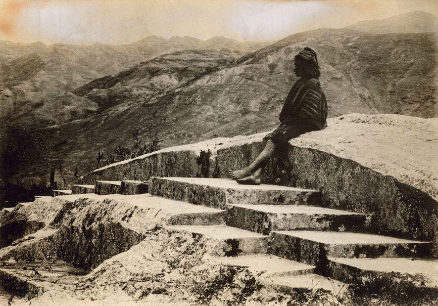 Un local peruano se sienta encima de la fortaleza inca de Saqsayhuamán con vista a Cusco, ...