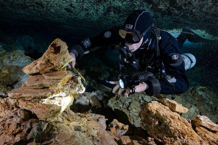 Un buzo examina las rocas apiladas por mineros antiguos que extrajeron pigmento ocre de La Mina, ...