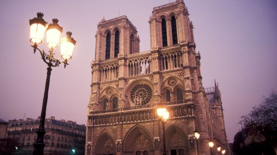 Una farola ilumina a Notre Dame al atardecer.