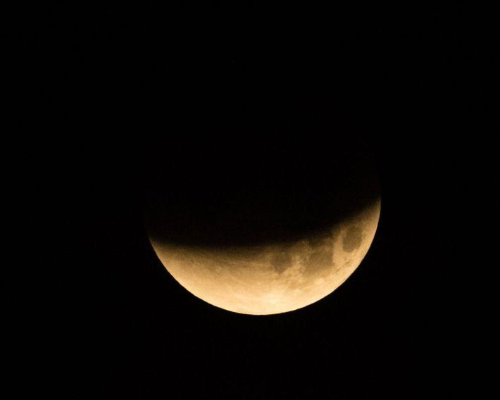 La sombra de la Tierra cae sobre la luna llena durante un eclipse lunar total en ...